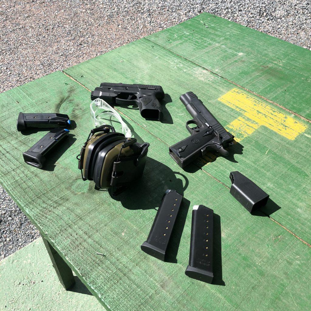 Armas de fogo em cima da mesa com protetor auricular eletrônico e óculos de segurança